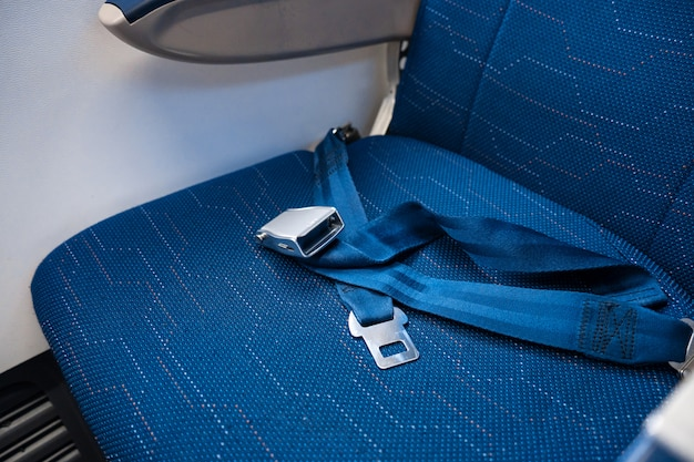 飛行機の空いている席の固定されていないシートベルト。飛行中の安全