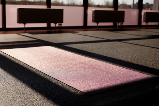 Разложенный фиолетовый коврик для йоги лежит на полу на полу, удобная открытая площадка для занятий спортом и физическими упражнениями