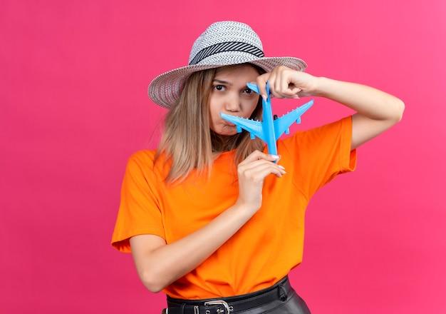 青いおもちゃの飛行機を持っている間悲しそうに見える日よけ帽をかぶったオレンジ色のtシャツを着た不幸なかなり若い女性