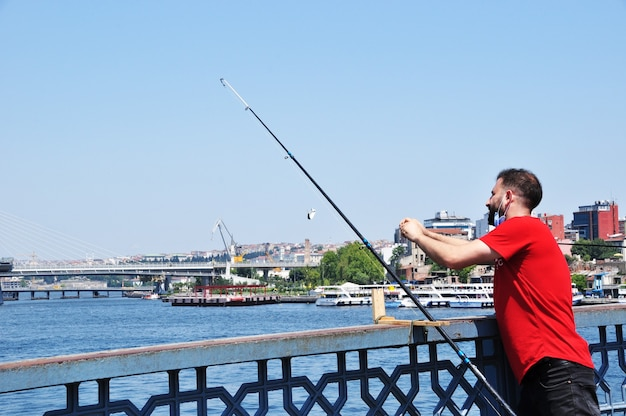 Неизвестный рыбак ловит рыбу с моста. мужчина ловит рыбу в стамбуле с галатского моста. ловит рыбу. 10 июля 2021 г., стамбул, турция
