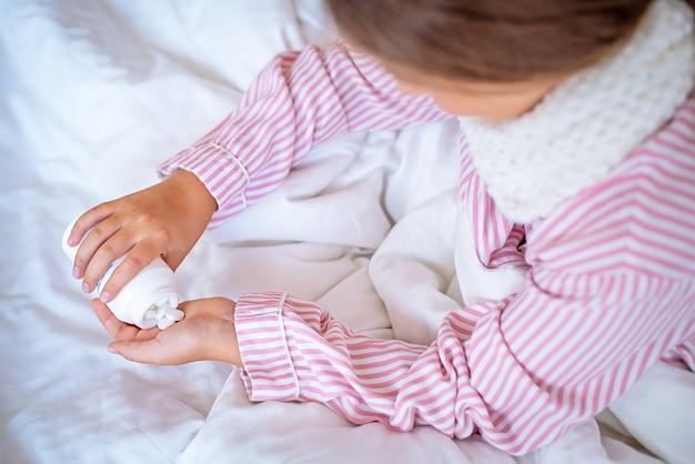 Неизвестная девушка, сидя на кровати, кладет ей в руку таблетки. вид сверху.