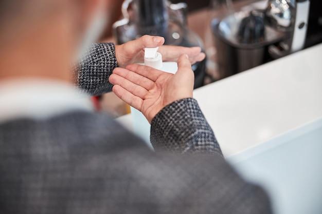 認識できない男が手を消毒するために液体消毒剤を手に入れている