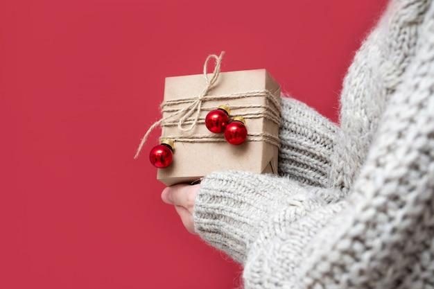스웨터를 입은 알아볼 수 없는 소녀가 빨간색 배경에 크리스마스 선물을 들고 있습니다. 여자의 손에 수제 선물 상자입니다. 아름 다운 선물과 함께 새 해 배경입니다.