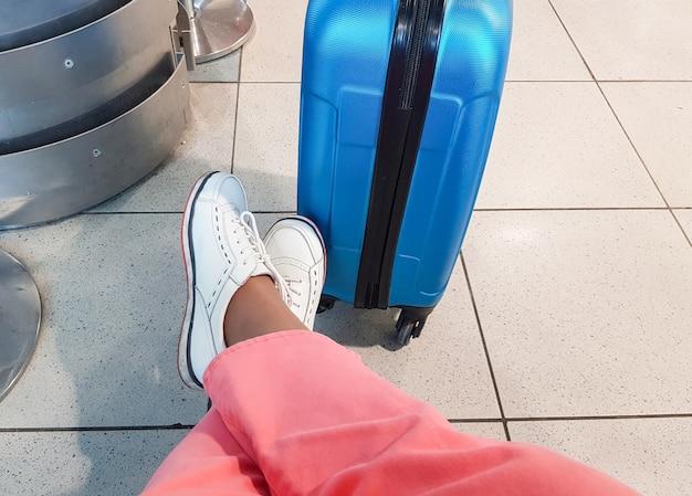 ピンクのズボンと白いスニーカーを身に着けた、見分けがつかない旅行者。リラックスしたポーズで座って、青いスーツケースの横に足を置き、旅行を待っています。