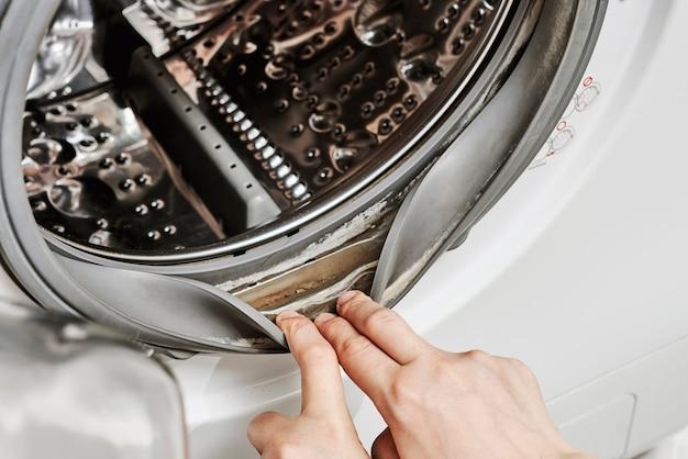알아볼 수 없는 여성이 세탁기를 청소합니다.