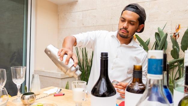 알아볼 수 없는 청년이 음료 교반기의 우유를 나무 탁자 위의 젖빛 유리 컵에 붓는다
