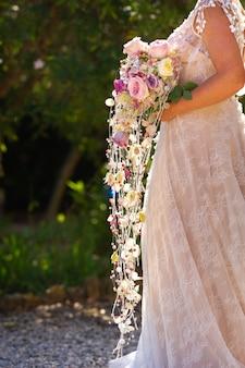 Необычный удлиненный свадебный букет в руках невесты.