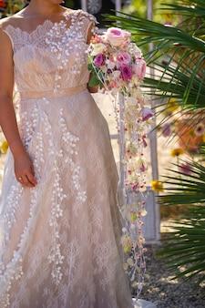 Необычный удлиненный свадебный букет в руках невесты