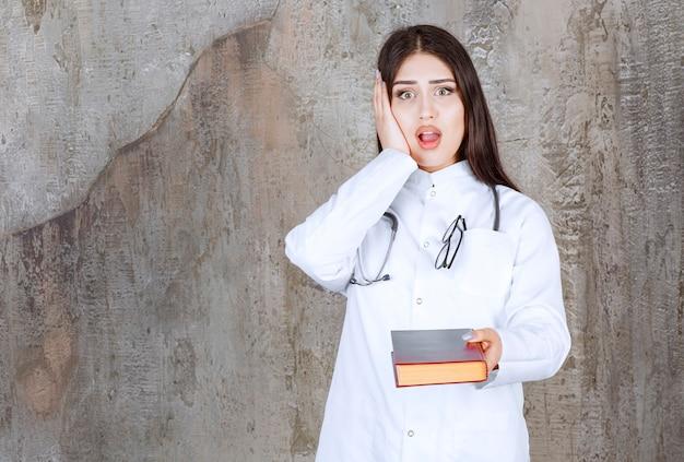 회색 벽에 자신의 머리에 그녀의 손을 잡고 화가 젊은 의사