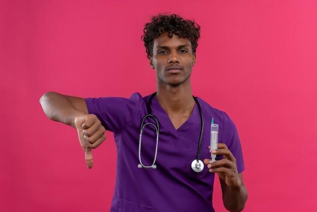 プラスチック注射器を押しながら親指を下に見せて聴診器で紫の制服を着た巻き毛の動揺の若いハンサムな浅黒い医者