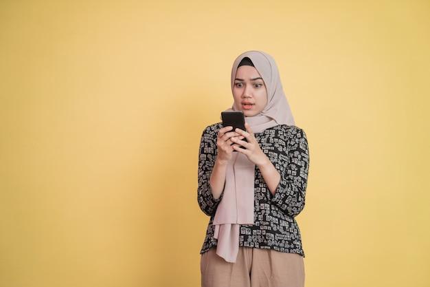 베일을 쓴 소녀가 카피스페이스가 있는 휴대폰 화면을 보고 놀란다