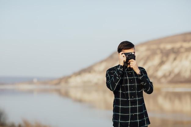 ヴィンテージ写真カメラ付きで山で写真を撮る