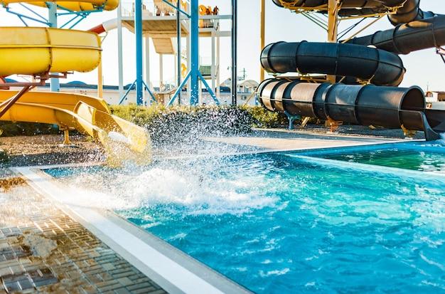 Женщина сошла с горки в бассейн с прозрачной водой