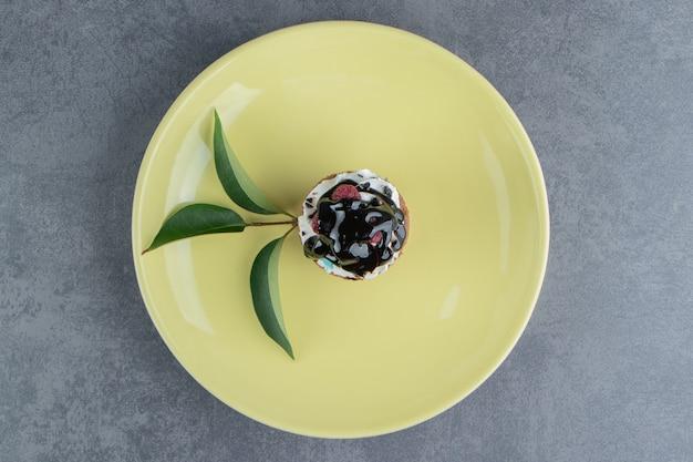 회색 표면에 맛있는 크림 컵 케이크와 함께 노란색 접시