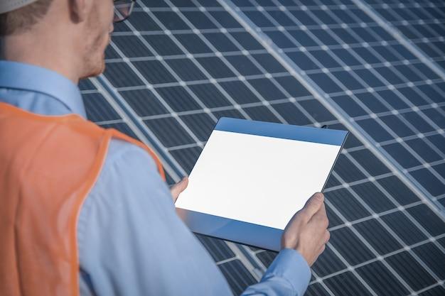 젊은 엔지니어가 석양에 태양 광 태양 광 패널 분야에서 태양의 작동과 청결을 태블릿으로 확인하고 있습니다.