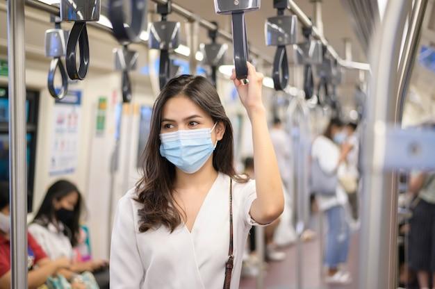 Молодая женщина носит защитную маску в метро, защита от covid-19, безопасное путешествие, новая норма, социальное дистанцирование, безопасный транспорт, путешествия в рамках концепции пандемии