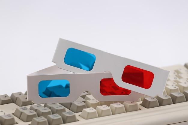 오래 된 pc 키보드에 anaglyph 3d 안경입니다. 흰색 배경. 레트로 속성 80년대