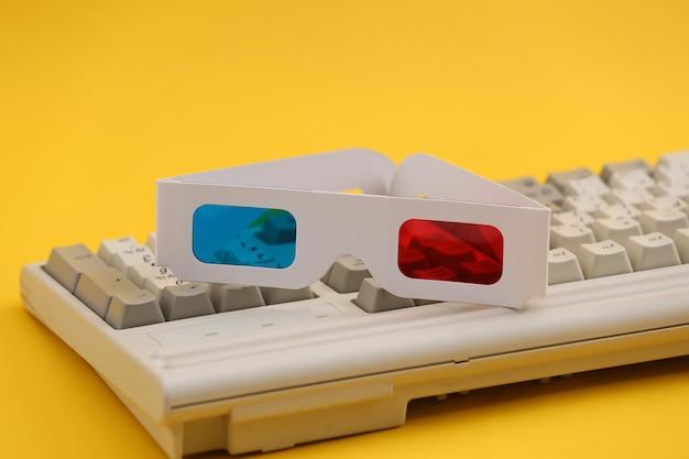 오래 된 pc 키보드에 anaglyph 3d 안경입니다. 노란색 배경입니다. 레트로 속성 80년대