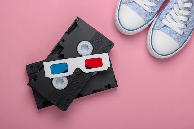 Одноразовые бумажные 3d очки anaglyph с кроссовками в олдскульном стиле и видеокассетой на розовом пастельном фоне. вид сверху. развлечения в стиле ретро 80-х