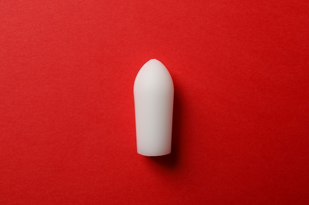 Anal or vaginal candle on red, close up
