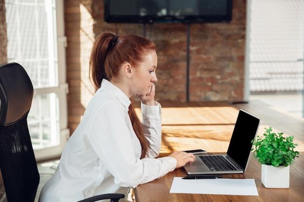 分析しています。オフィスで働くビジネス服装の白人の若い女性