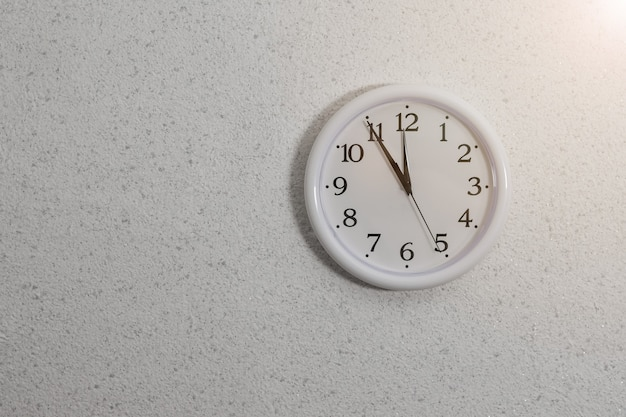 Analog clock with hands on the wall with textured plaster. device for determining the time.