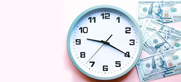 アナログの白い時計とドル