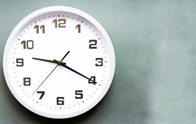 Analog white clock on a gray background
