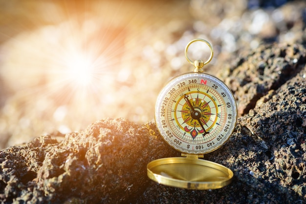 Analogical compass abandoned on the rocks with blurred sea background
