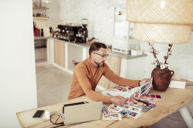 Анализирую работу. серьезный модельер сидит за столом, рассматривает свои эскизы и сравнивает фотографии платьев.