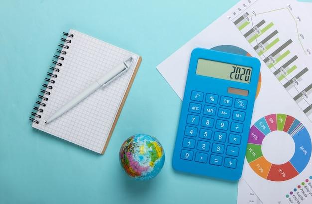 Анализ мировой статистики. глобус, калькулятор, графики и диаграммы, ноутбук на синем фоне. вид сверху. плоская планировка