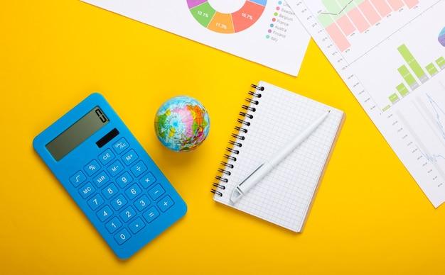 Анализ мировой статистики. глобус, калькулятор, графики и диаграммы, ноутбук на желтом фоне. вид сверху. плоская планировка