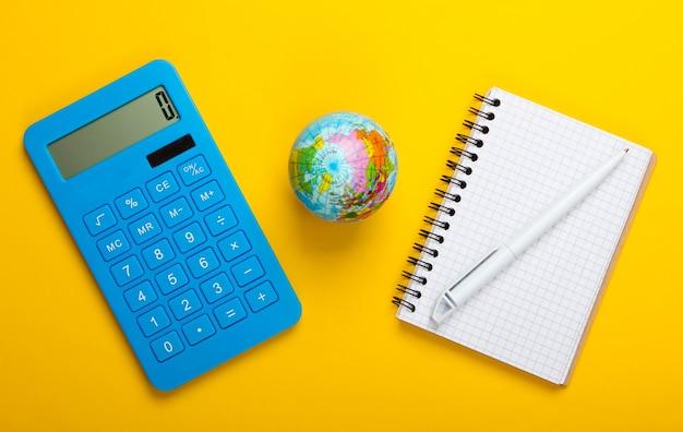 Анализ мировой статистики. глобус, калькулятор, тетрадь на желтом фоне. вид сверху. плоская планировка