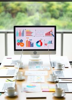 分析販売目標成長グラフチャート投資レポートデータは、背景がぼやけた庭の景色を望む正面のガラスの建物の窓の会議テーブルの中央に配置された大きなコンピューター画面モニターにあります。