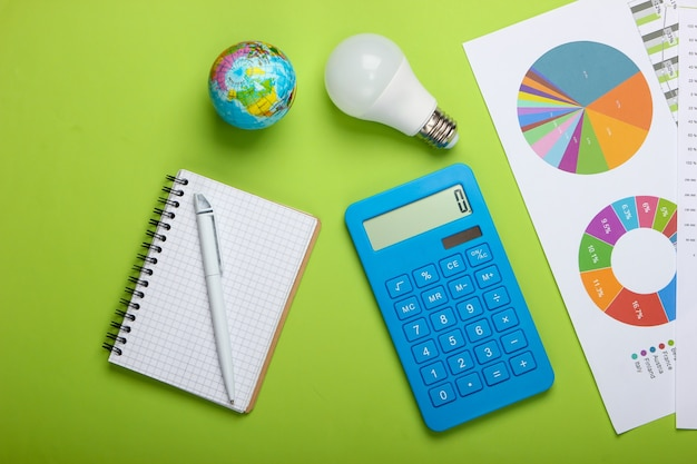 Analysis and statistics of energy consumption. eco concept. economy. calculator with graphs and charts, energy-saving light bulb, globe, notepad on green background. top view
