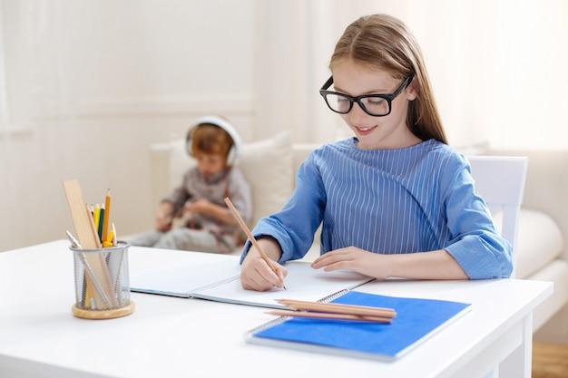 テーブルに座って、彼女の兄弟が彼女の後ろのソファでタブレットで遊んでいる間、彼女の家の割り当てに取り組んでいる分析的な野心的な才能のある子供