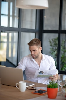 Analytical work. a concentrated man checking figures in the report