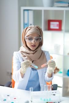 Анализ химикатов. женщина-химик в хиджабе чувствует себя занятой анализом химикатов в пробирках