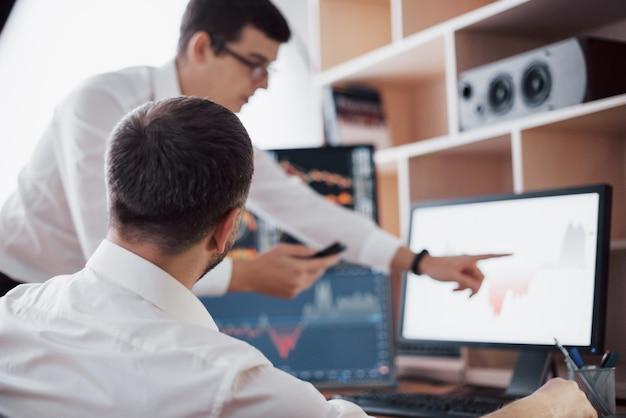データの分析。若い女性がペンでチャートに提示されたデータを指している間、クリエイティブオフィスで一緒に働いている若いビジネスチームのクローズアップ。