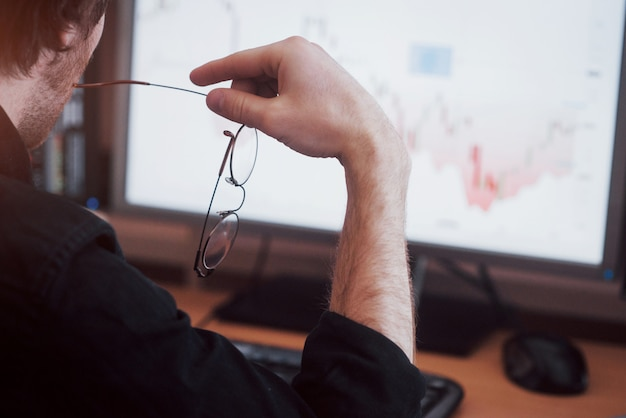 Analyzing data. close up of a young businessman who holds glasses and looks at the gff while working in a creative office