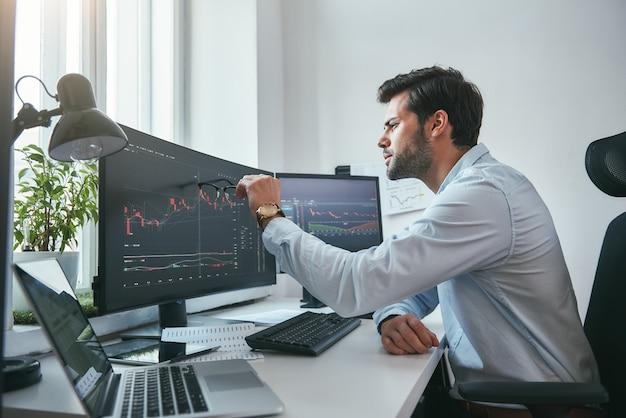 데이터 분석 사려 깊은 젊은 상인이 작업하는 동안 컴퓨터 화면의 그래프를 가리키고 있습니다