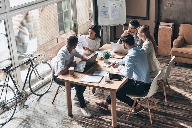 Анализируем данные. вид сверху молодых современных людей в элегантной повседневной одежде, обсуждающих бизнес, сидя в творческом офисе