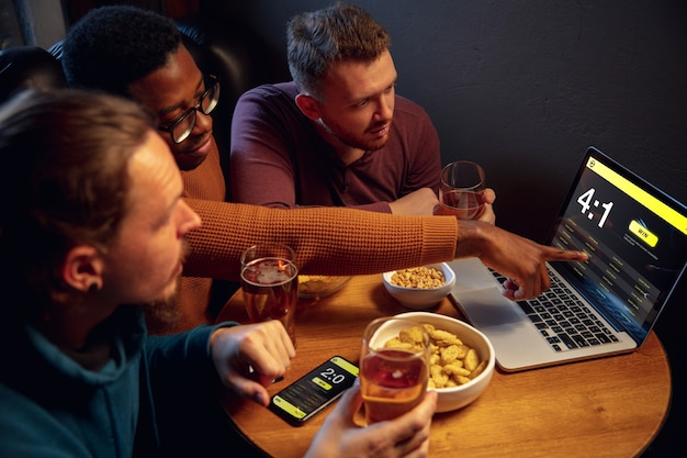 Analyzing. excited fans in bar with beer and mobile app for betting, score on their devices. screen with match results, emotional friends cheering. gambling, sport, finance, modern techn concept.