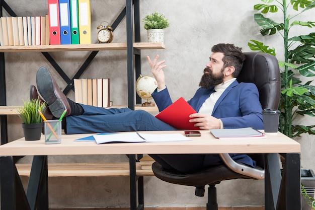 財務報告の分析。財務報告。中小企業の所有者。男ひげを生やしたビジネスマンは、オフィスに座ってビジネスレポートを読みます。会計と銀行。ガイバンカー会計士は指標マーカーを学びます。