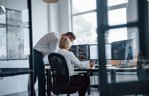 Совместно анализируем информацию. два биржевых маклера в формальной одежде работают в офисе с финансовым рынком.