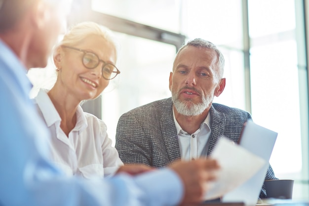 Анализируя отчет успешных деловых людей, работающих вместе, сидя за столом в современном офисе