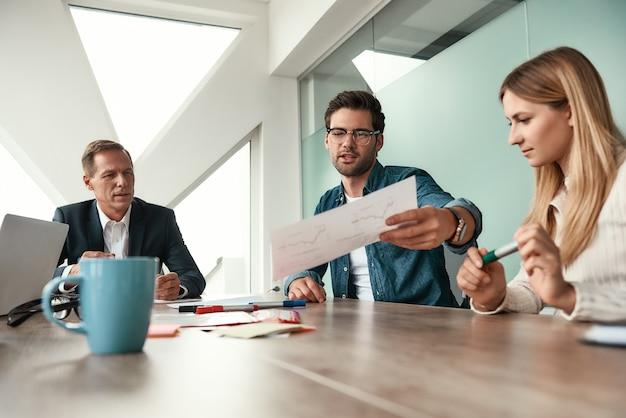 結果の分析。オフィスのテーブルに座っている間彼の同僚に財務報告を示す眼鏡の若い男。社会人。ブレーンストーミング