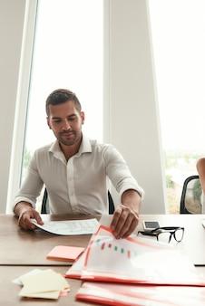 結果を分析するオフィスに座っている間、財務報告を保持しているフォーマルな服装の若い男性