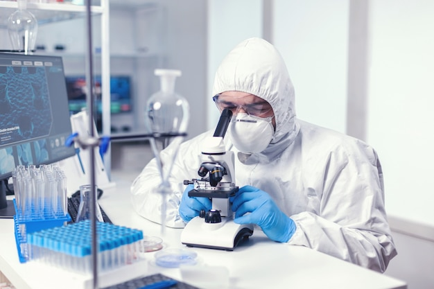 Analyzing virus in microbiology lab using microscope wearing ppe suit and glasses