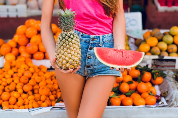 Ananas and slice of watermelon in hands of girl on tropical fruits market
